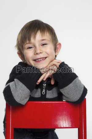 portrait of boy leaning on red