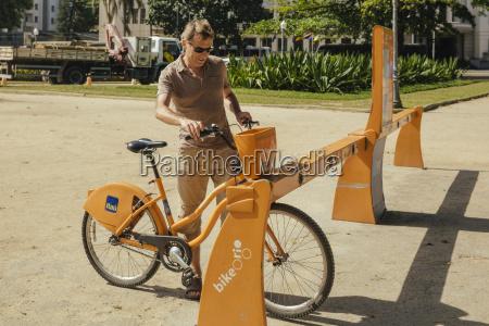 man renting a public transportation bicycle