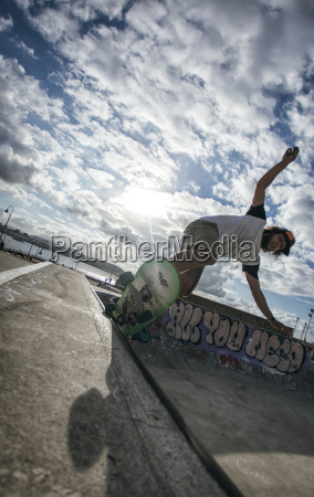 young man skateboarding in a skatepark