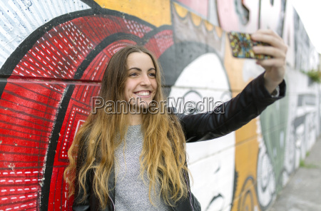 smiling teenage girl taking a selfie
