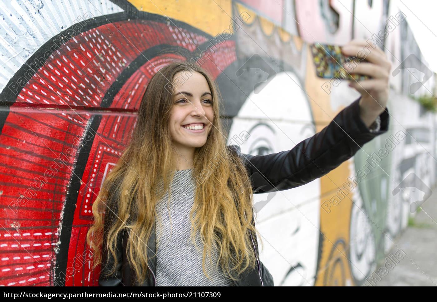 lächelndes, teenager-mädchen, nimmt, ein, selfie, bei - 21107309