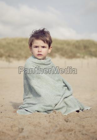 kleiner junge der auf dem strand