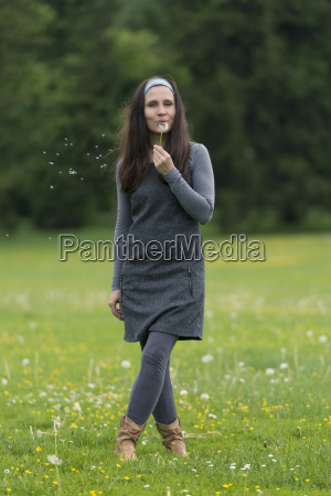 young woman standing on meadow with