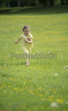 little girl running on meadow with