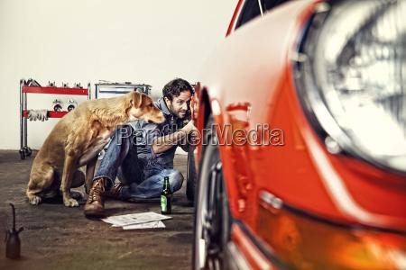 man repairing his vintage car