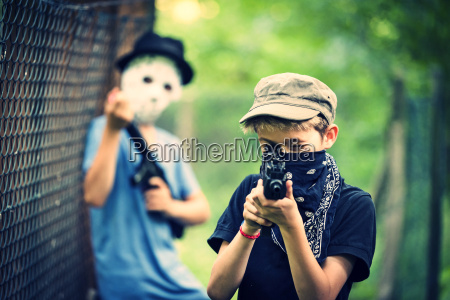 masked boy aiming with toy gun