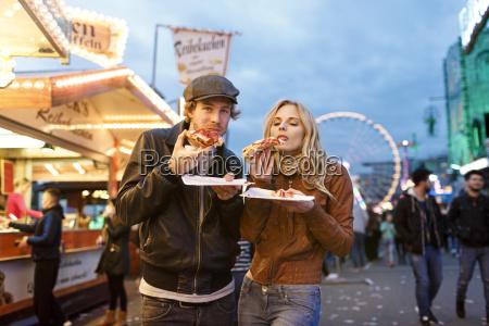 junges paar auf spassiger messe pizza