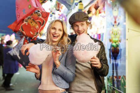 young couple at fun fair eating