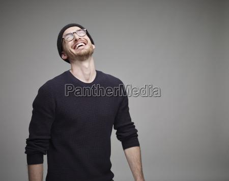 portraet eines lachenden mannes mit wollmuetze
