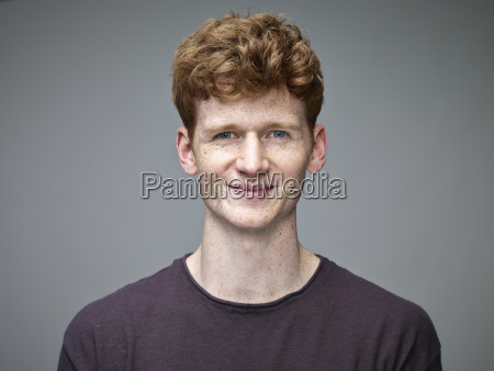 portrait of smiling redheaded young man