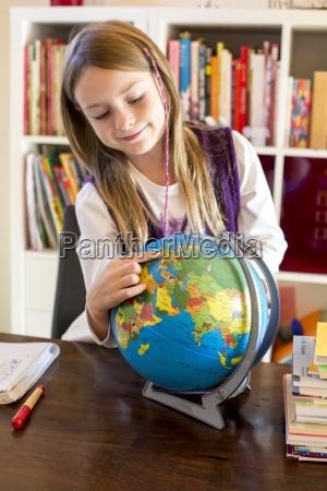 maedchen zeigt auf globus