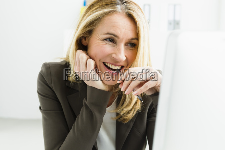 germany bussinesswoman looking at monitor smiling