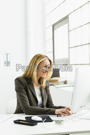 germany businesswoman using computer smiling