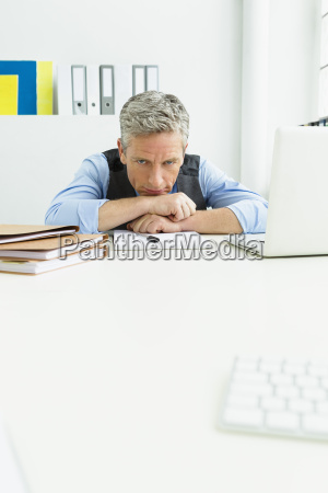 germany tired businessman leaning on desk