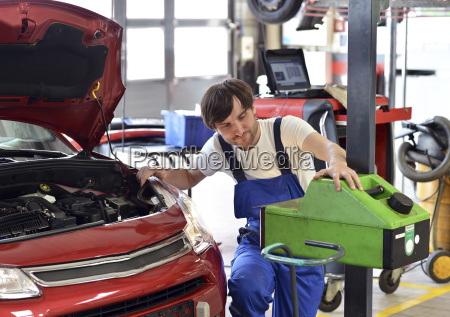 car mechanic adjusting headlight