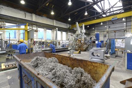 arbeiter in einer fabrikhalle mit cnc