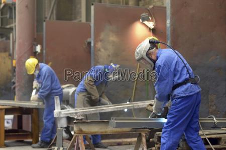 arbeiter entgraten gusseisenteile in einer giesserei