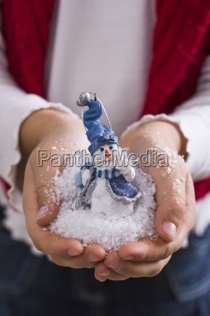 hands of little girl holding snow