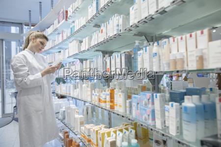 junger apotheker in der apotheke waehlt