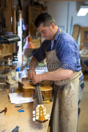 guitar maker in his workshop