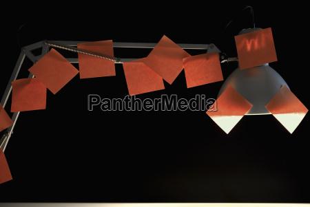 schreibtischlampe mit vielen roten klebeetiketten