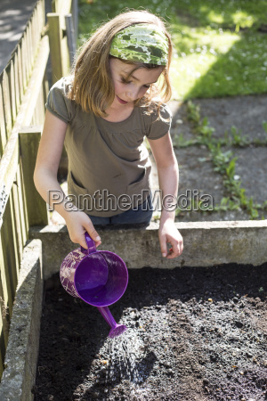 portrait of girl pouring seeds in