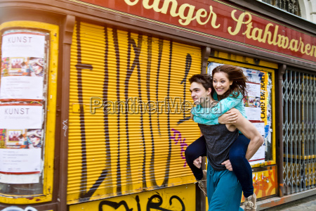 young man carrying girlfriend in the