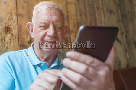 portrait of senior man using phablet