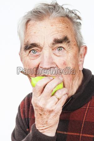 portrait of senior man eating pear