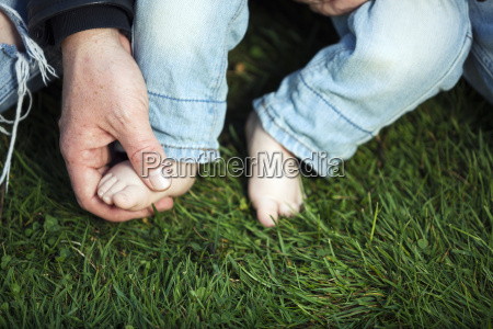 father holding foot of his little