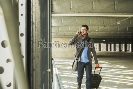 young businessman walking in car park