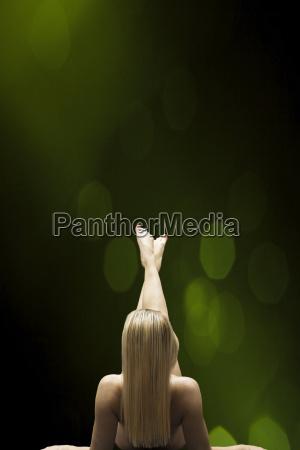 female nude in front of dark