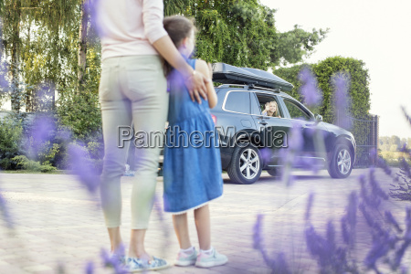 mother and daughter watching car driving