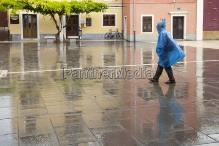 slowenien koper frau mit regencape ueberquert