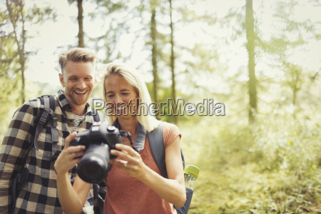 smiling couple hiking viewing digital slr