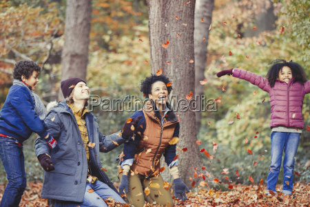 playful young family throwing autumn leaves