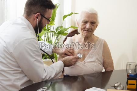 doctor examining an old woman with