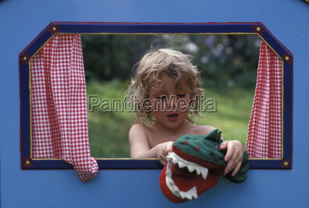 girl playing with crocodile hand puppet