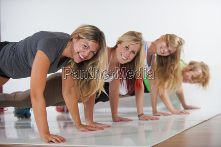 women and teenage girl exercising smiling