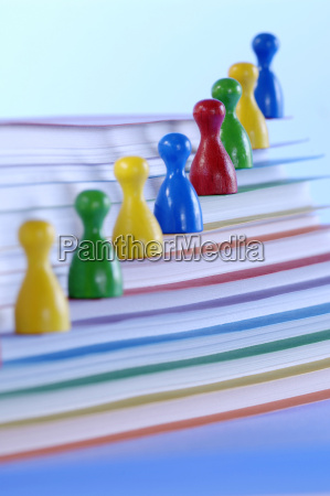 game pieces on stack of papers