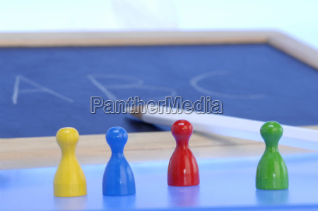tafel mit bleistift und spielfiguren nahaufnahme