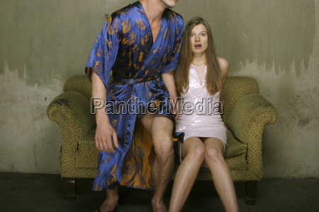 woman sitting on couch while man