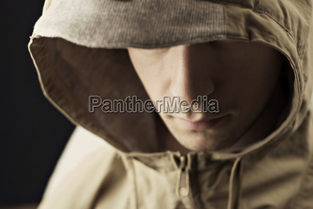 young man wearing hood jacket close