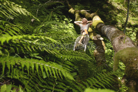 young woman relaxing on tree trunk