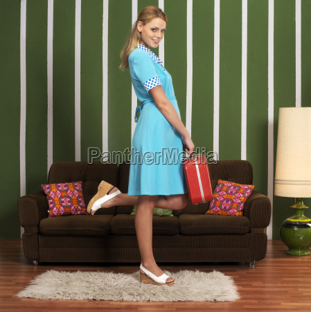 young woman standing with suitcase smiling