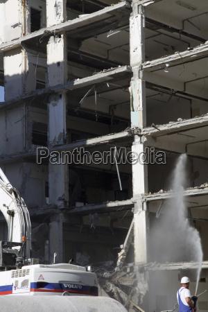 germany berlin man watering on demolished