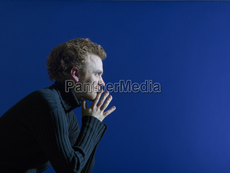 young man sitting against blue background