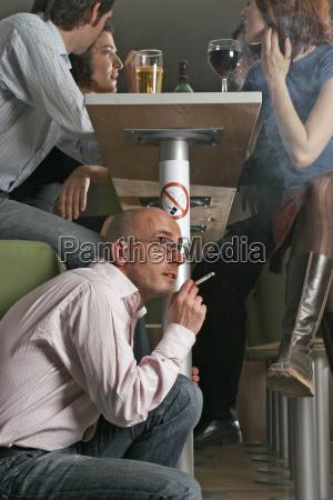 mann raucht zigarette neben rauchverbot