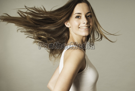 young woman in sportswear tossing hair