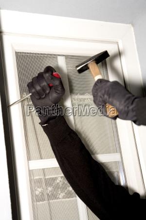 burglary hand with gloves on window